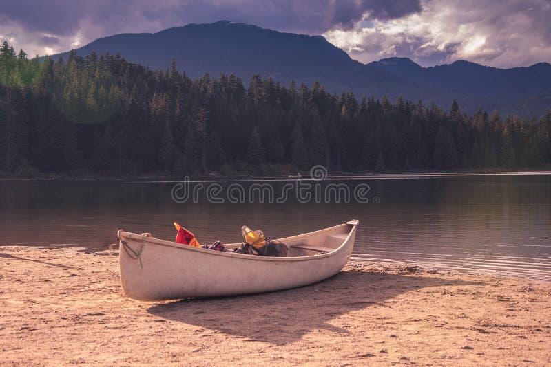 Canoe a lo largo de orilla del lago ocultado en marmota, Columbia Británica imagenes de archivo
