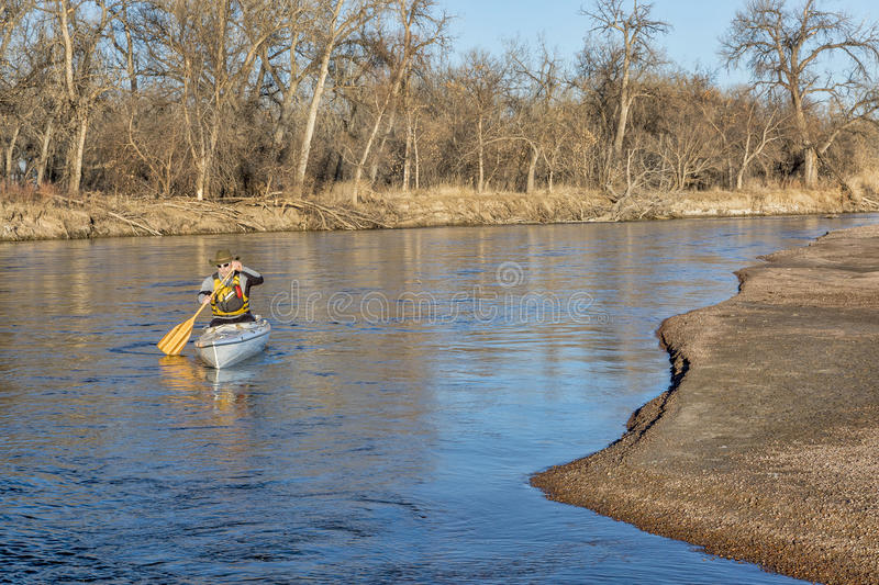 Canoe paddling on South Platte RIver. Senior paddler in a decked expedition canoe on the South Platte River in eastern Colorado, winter scenery without snow stock photography