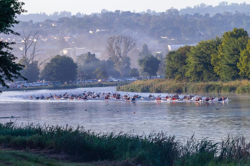 Canoe Race Paddlers River Start Line Paddling. Canoe Race men athletes doubles paddlers paddling from starting line on river water at dawn landscape  photo royalty free stock photo