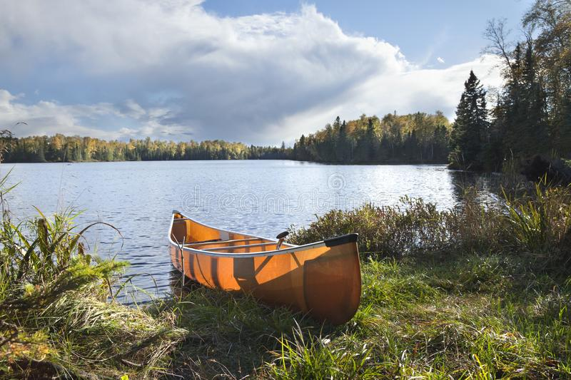 Canoe on the shore of a northern Minnesota lake during autumn. Canoe on the shore of a beautiful northern Minnesota lake during autumn royalty free stock photo