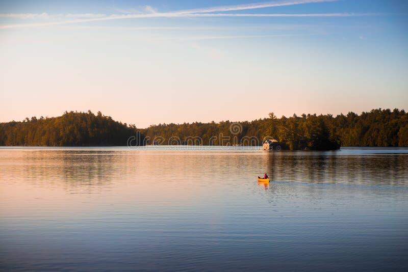 Canoe sul lago tranquillo Joseph, Muskoka, all'alba immagine stock libera da diritti