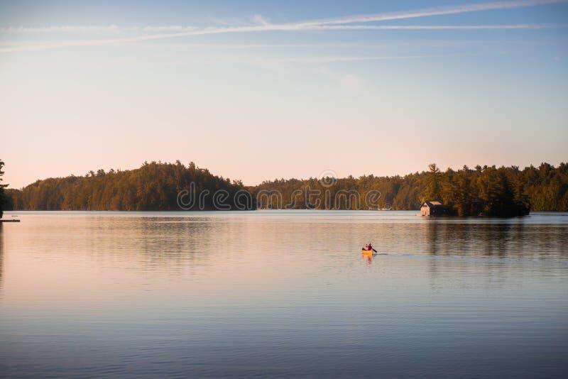 Canoe sul lago tranquillo Joseph, Muskoka, all'alba immagini stock libere da diritti