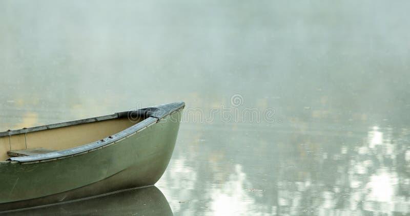 Canoe sull'acqua vetrosa con nebbia, spazio negativo per testo immagini stock
