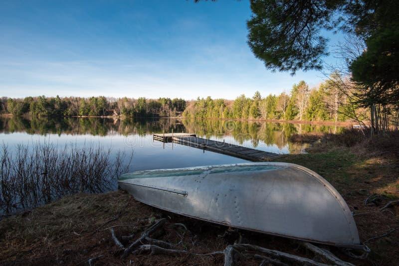 Canoe sulla riva di un lago liscio fotografia stock