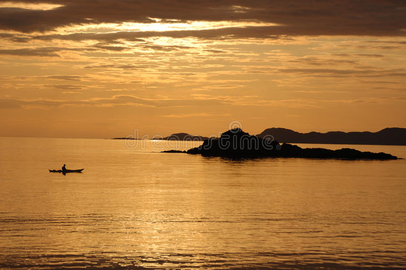 Canoe sunset at Arisaig. A lone canoeist at sunset from the shoreline at Arisaig, Scotland stock photo
