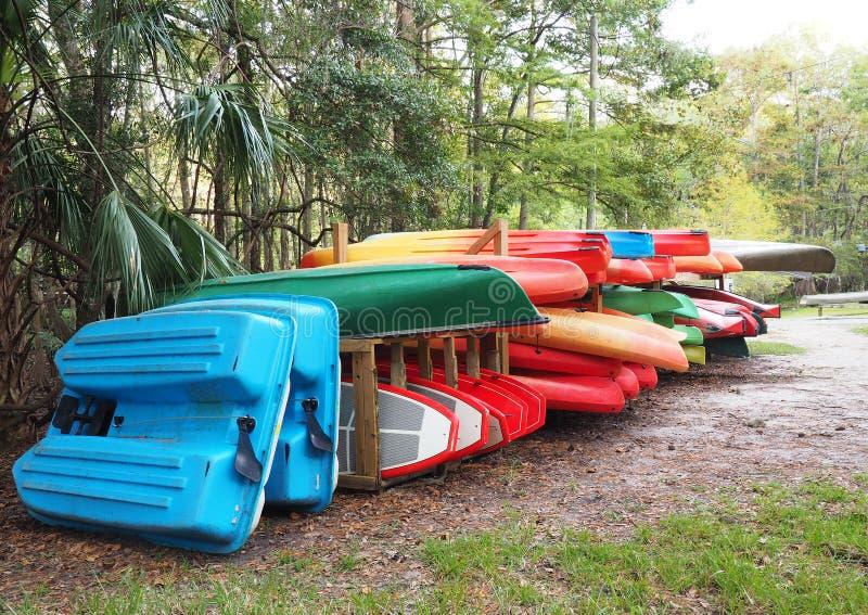 Canoe variopinte, kajak e barche nell'arrivo aspettante dello scaffale immagini stock libere da diritti