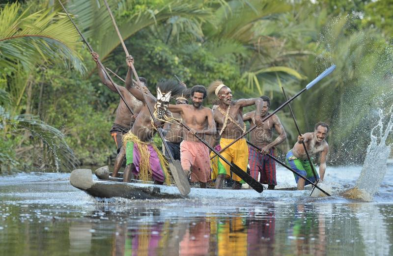Canoe war ceremony of Asmat people. Headhunters of a tribe of Asmat. INDONESIA, IRIAN JAYA, ASMAT PROVINCE, JOW VILLAGE - JUNE 23: Canoe war ceremony of Asmat royalty free stock photos