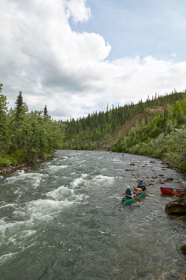 Canoeing на речных порогах реки в одичалой, удаленной Аляске стоковые фото