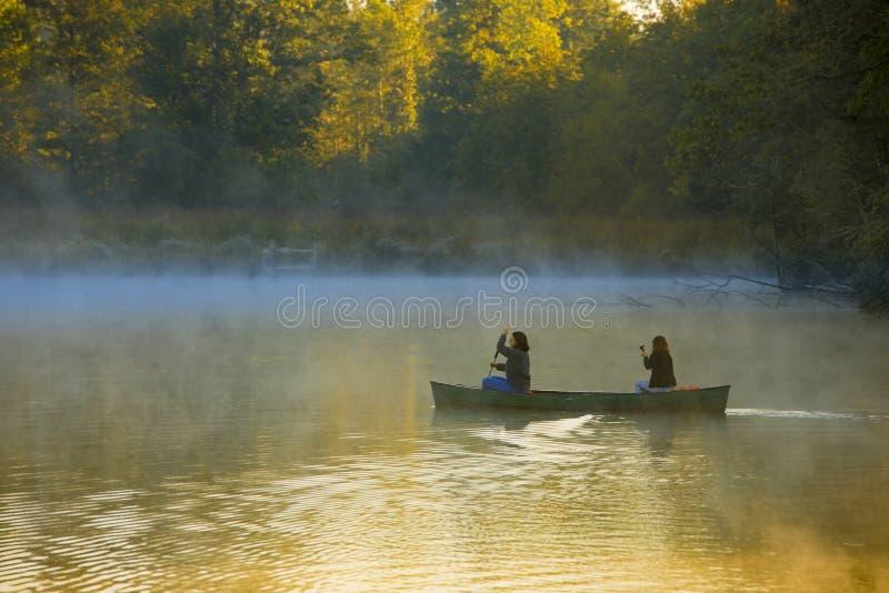 Canoeing через туман утра стоковые изображения