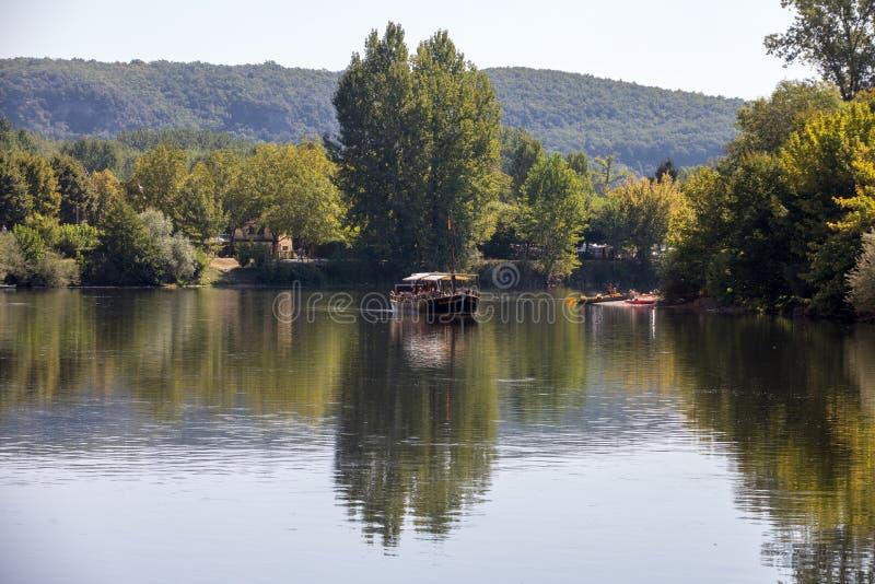 Canoeing en toeristenboot, in Frans geroepen gabare, op de rivier Dordogne bij La roque-Gageac, Aquitaine, Frankrijk stock foto