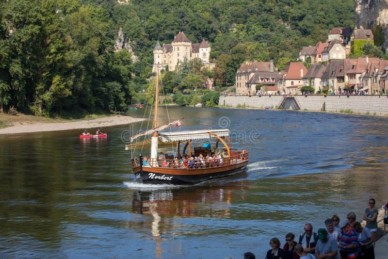 Canoeing en toeristenboot, in Frans geroepen gabare, op de rivier Dordogne bij La roque-Gageac en Chateau-La Malartrie in backg royalty-vrije stock foto
