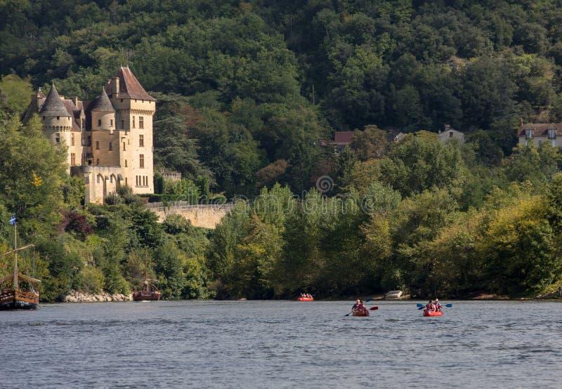 Canoeing en toeristenboot, in Frans geroepen gabare, op de rivier Dordogne bij La roque-Gageac en Chateau-La Malartrie in backg royalty-vrije stock fotografie