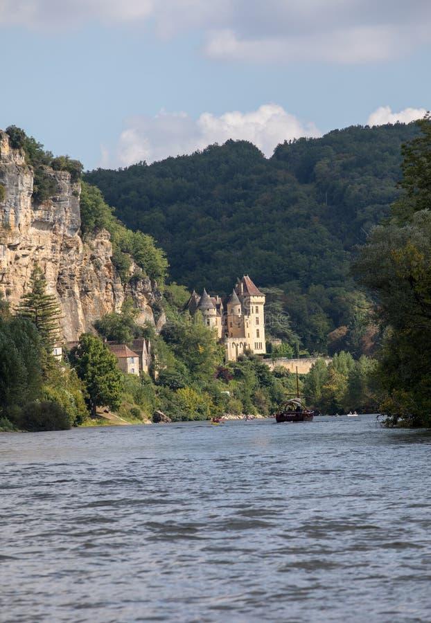 Canoeing en toeristenboot, in Frans geroepen gabare, op de rivier Dordogne bij La roque-Gageac en Chateau-La Malartrie in backg stock fotografie