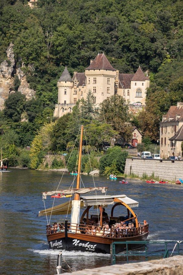 Canoeing en toeristenboot, in Frans geroepen gabare, op de rivier Dordogne bij La roque-Gageac en Chateau-La Malartrie in backg royalty-vrije stock foto's