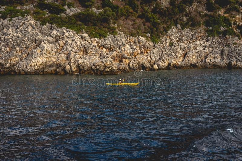 Canoeing and kayaking in the sea near a mountain island. Distant, canoe, kayak, sport, people, swimming, paddling, Greece royalty free stock photography
