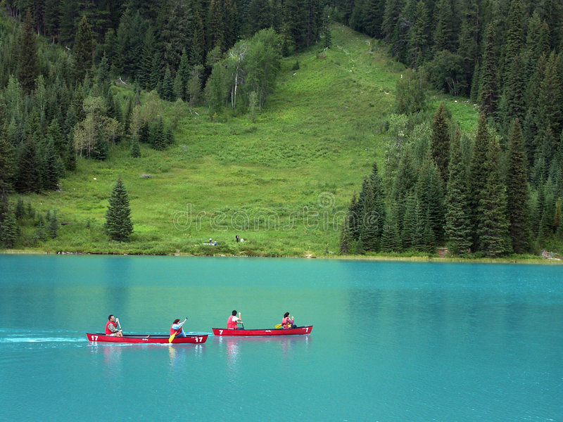 Canoeing sul lago verde smeraldo, il Canada fotografia stock
