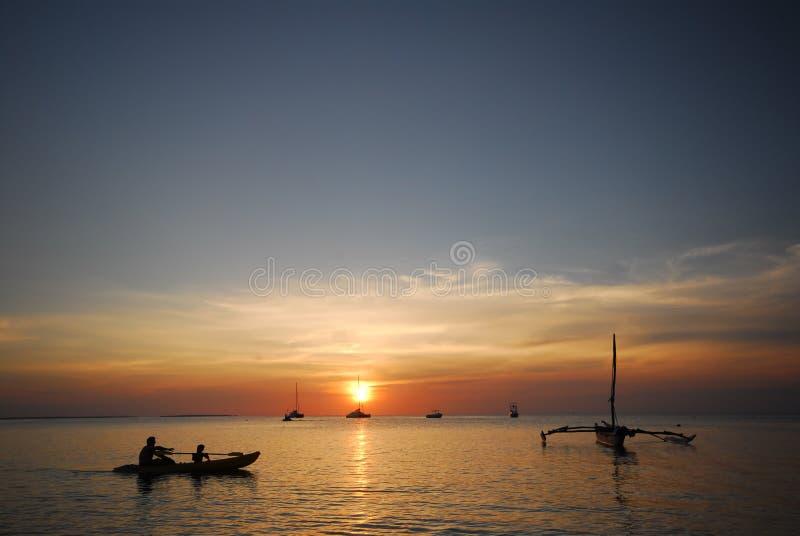 Canoeing van de zonsondergang stock afbeeldingen