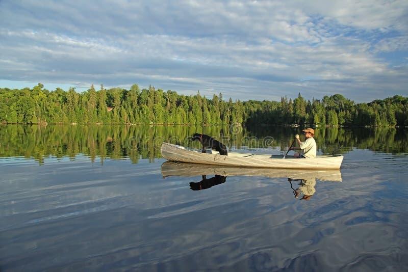 Canoeist avec le chien d'arrêt de Labrador dans la proue photographie stock libre de droits