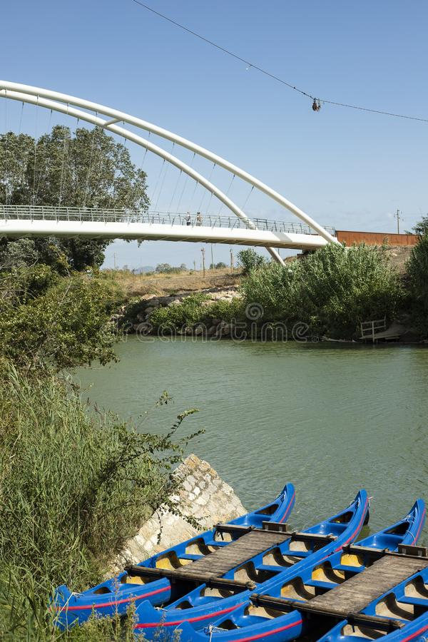 Canoes anchored at harbour in green river with the bridge in the background. Maremma, Tuscany, Italy. Canoes anchored at harbour in the green Ombrone river, idea royalty free stock image