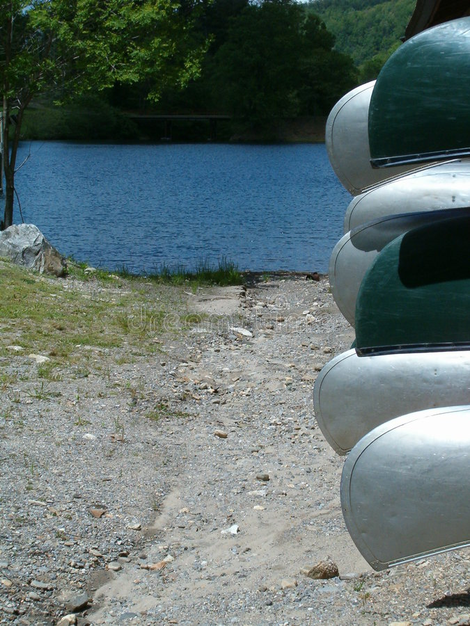 Canoes and lake. A stack of canoes with a lake (river) in the background stock photography