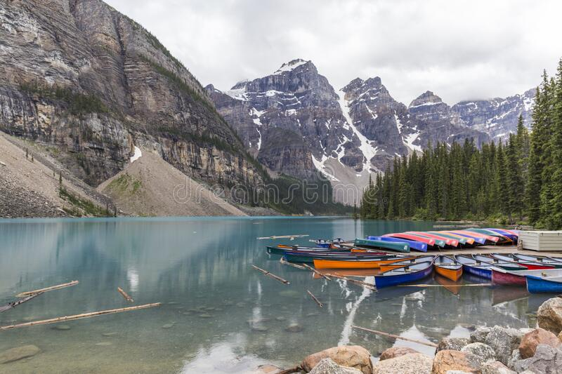 Canoes in the lake. Canoes of different colors docked on a jetty of a turquoise water lake with high mountains on a cloudy day stock image