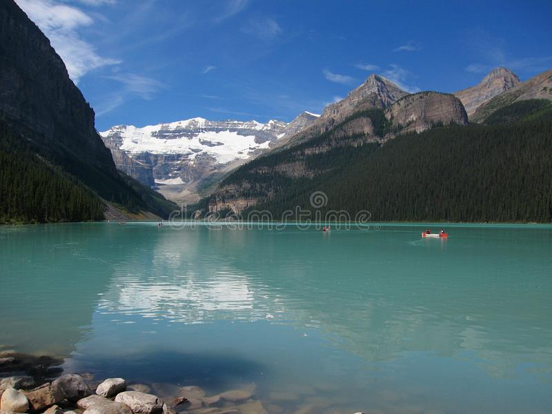 Canoes on Lake Louise with Victoria Glacier and Mountain Landscape, Banff National Park, Alberta. Canoes on glacial Lake Louise with its turquoise waters and royalty free stock photos