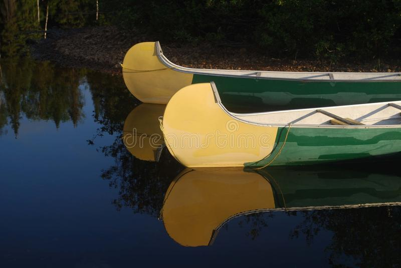 Canoes and light. Two canoes in a wild lake royalty free stock photo
