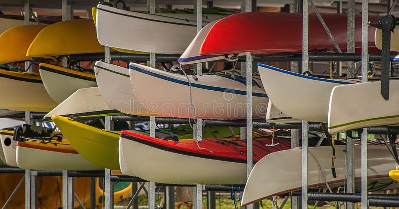 Canoes piled in a steel rack. Various canoes have been stored in a steel rack. They are next to each other and stacked and are ready to be rented out to stock photos