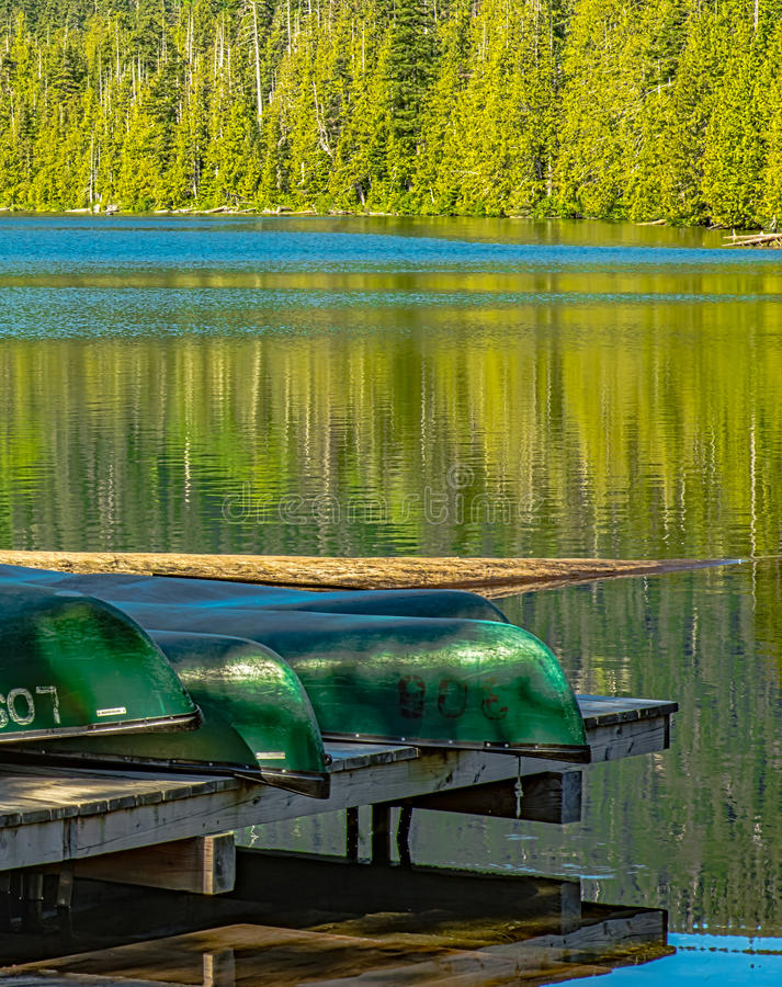 Canoes ready for Happy Campers. Canoes are ready for another fun day at a summer resort in the Oregon Cascades royalty free stock photo