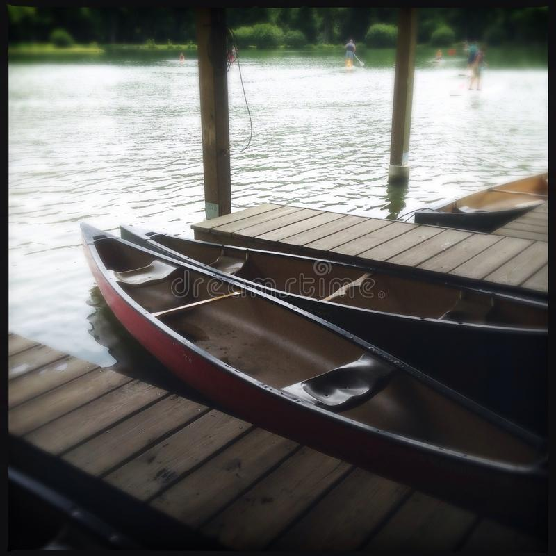 Canoes by the side of a lake stock image