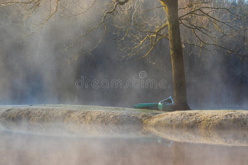 Canoes waiting by the tree royalty free stock photo