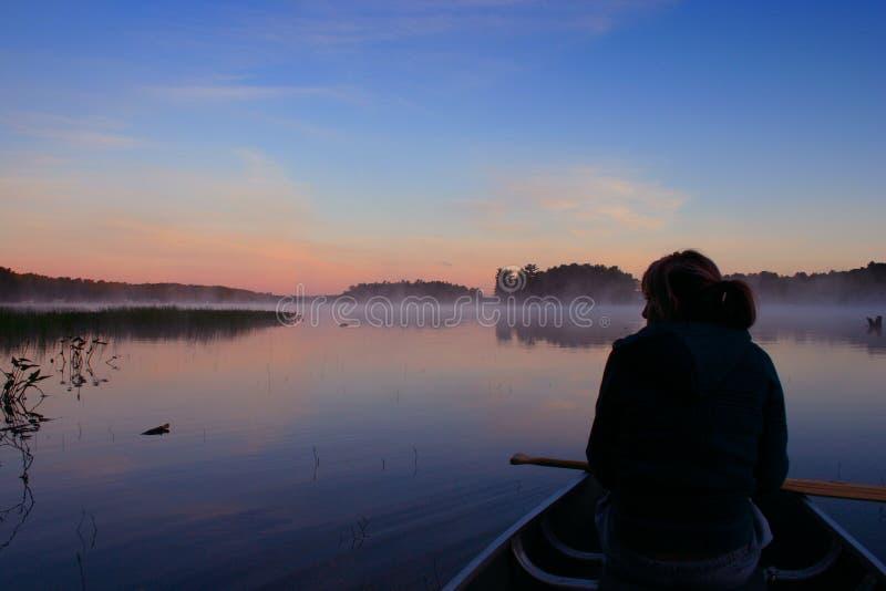 canoing восход солнца девушки стоковые фотографии rf