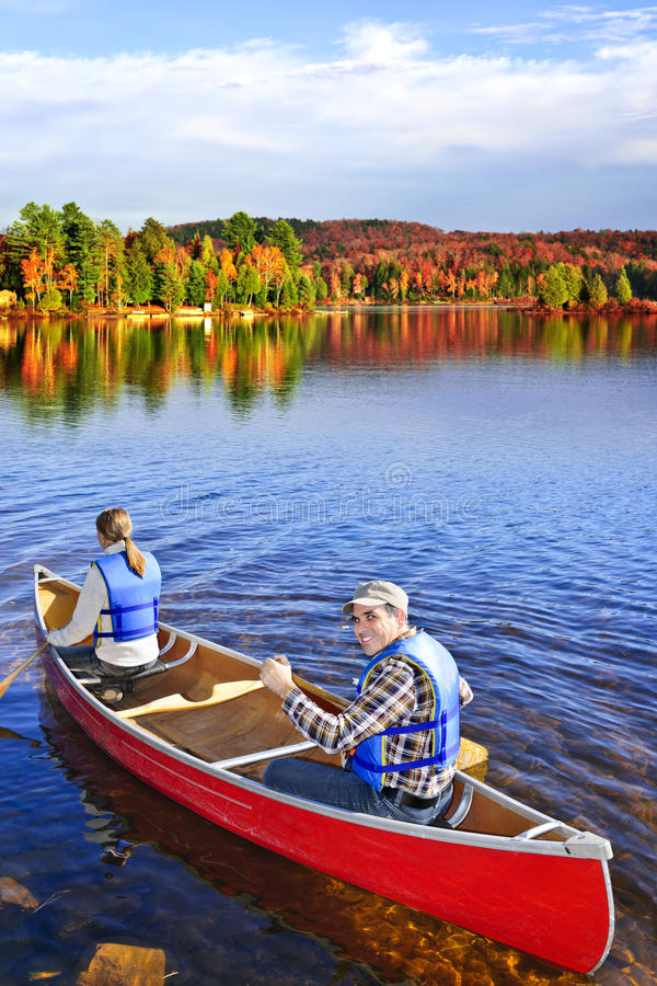Canoing in fall. People canoeing on scenic lake in fall, Algonquin park, Canada royalty free stock photos