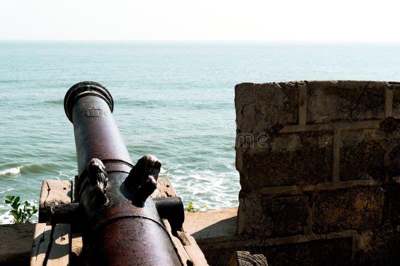 Canon antique en métal faisant face à la mer ouverte d'un mur en pierre de château image stock