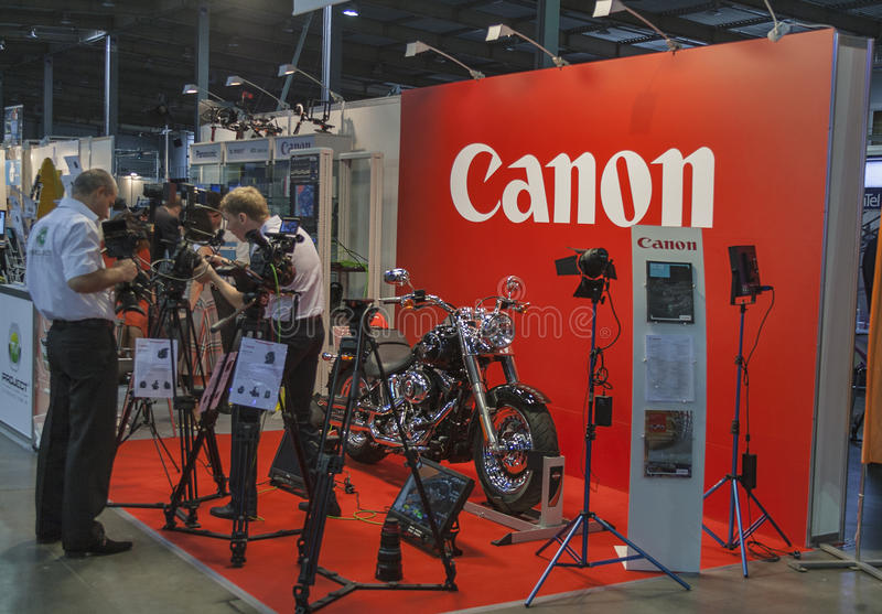 Canon booth. Visitors visit Canon TV and photography equipment booth with Harley-Davidson motorcycle at Kyiv International TV and Radio Fair 2013. It is the main royalty free stock images