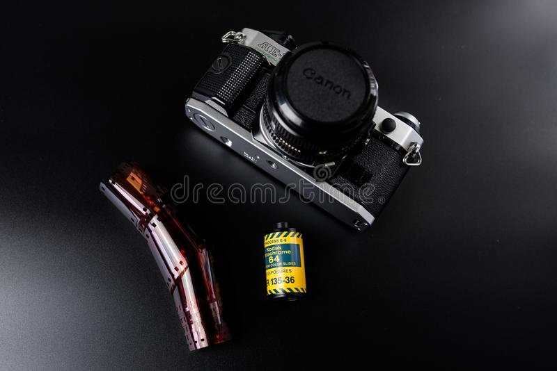 Canon film camera with Kodak slide film. A classic Canon AE-1 Program 35mm film camera with a roll of Kodak Echtachrome slide film and a developed film strip on stock image