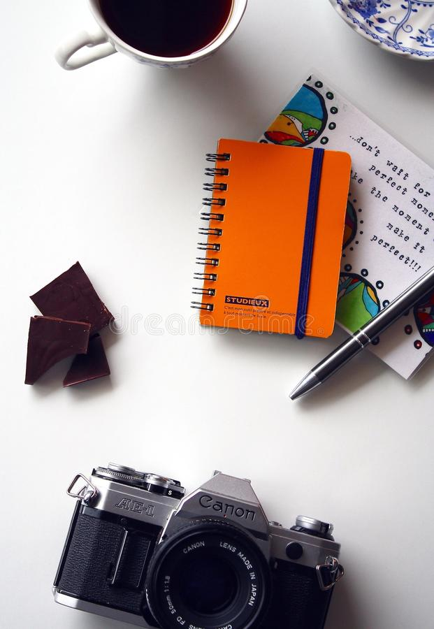 Canon Gray and Black Bridge Camera Near Orange and Blue Spiral Notebook royalty free stock image