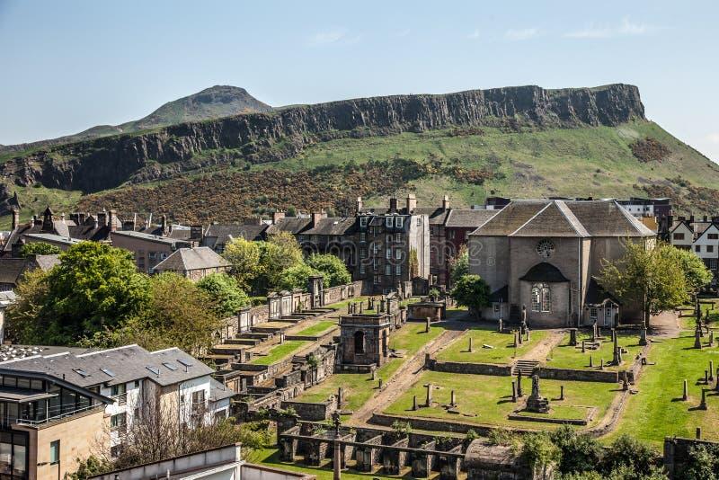 Canongate Kirk och Salisbury brant klippa, Edinburg, Skottland royaltyfri bild