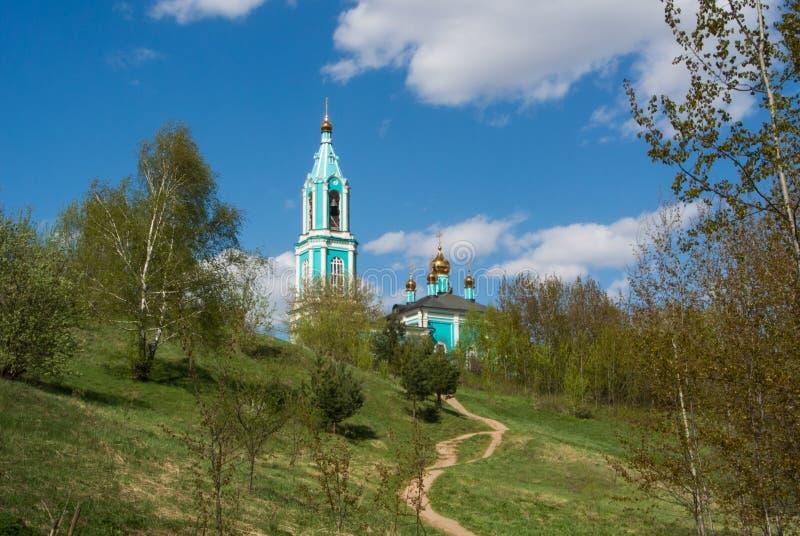 Canonic sikt av den lilla ryssortodoxkyrkan över kullen, det härliga sommarlandskapet med träd och en bana royaltyfri foto