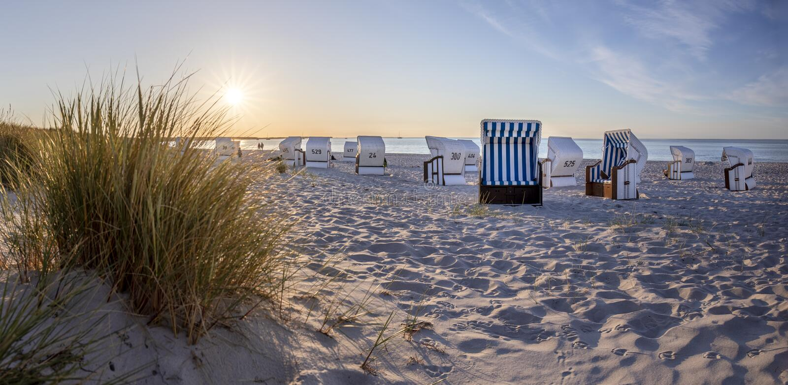Canopied beach chairs at beach near Prerow  in evening light royalty free stock photos