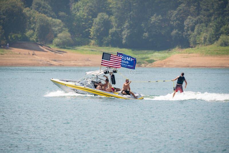 Canot automobile avec des drapeaux d'Américain et de pro-atout sur le lac photographie stock