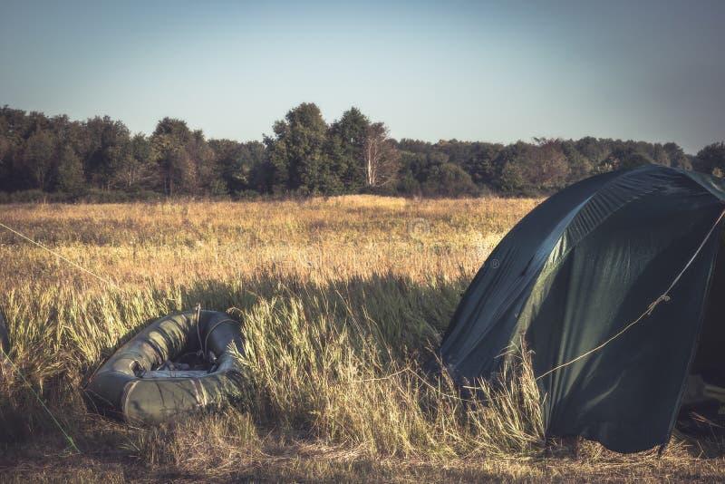 Canot en caoutchouc de tentes de camping de camping sur le champ d'été pendant des vacances de camping au lever de soleil image stock