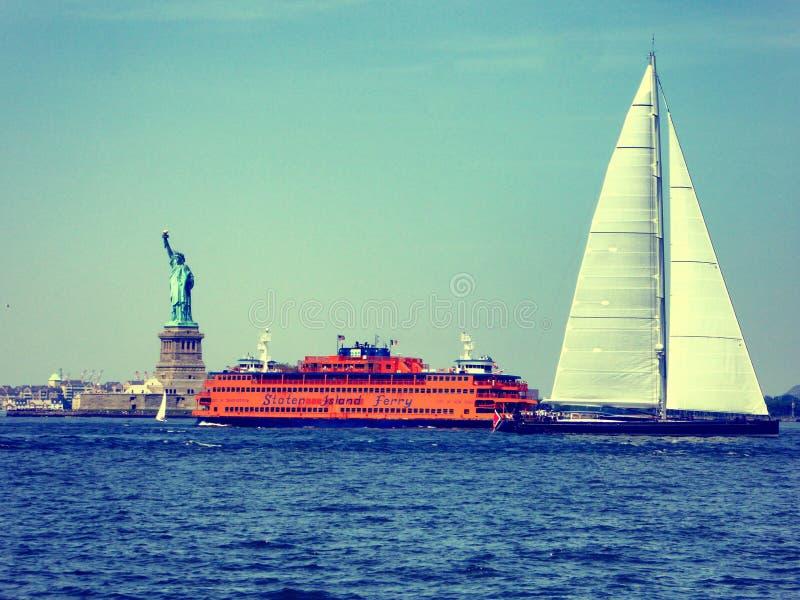 Canottaggio del traghetto della Staten Island e di Sailingboat vicino alla statua della libertà fotografie stock libere da diritti