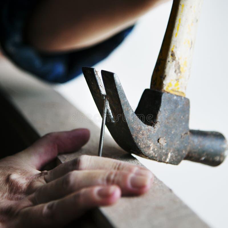 Canpenter utilisant la traction de marteau un clou d'un bois photos libres de droits