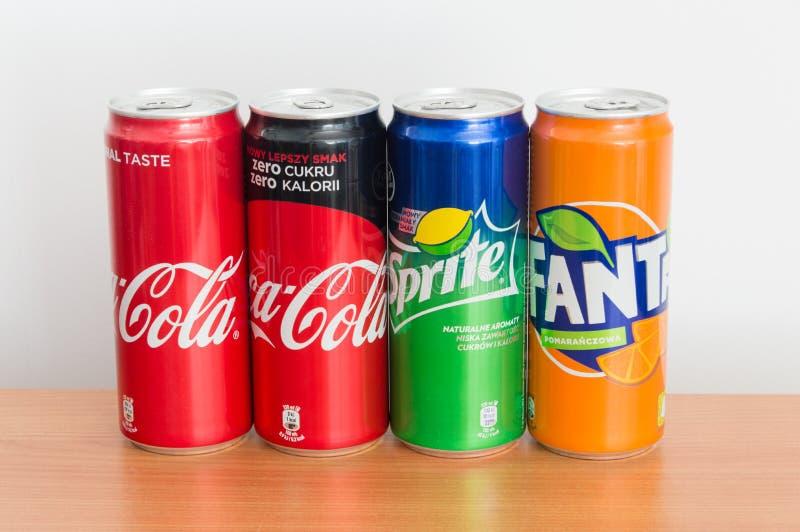 Cans av cocaen - cola, coca - cola noll, Sprite och Fanta på trätabellen arkivbild