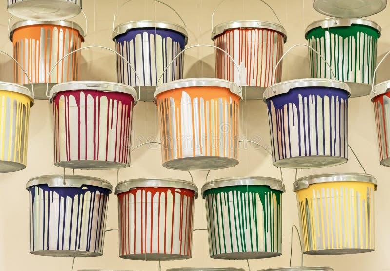 Cans med flerfärgade droppar från en färg Droppar och spill på målarhinkar arkivfoto