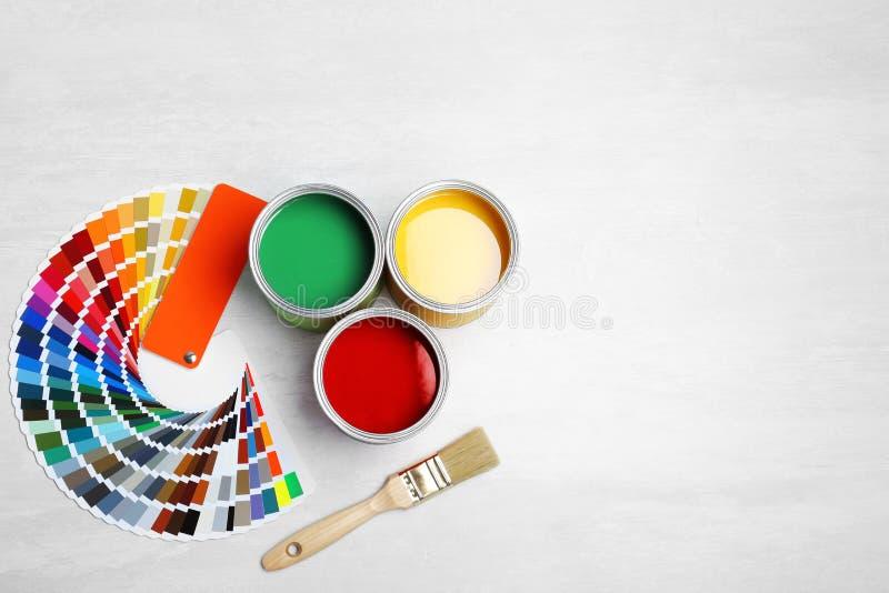Cans med målarfärg, borsten och färgpaletten royaltyfria foton