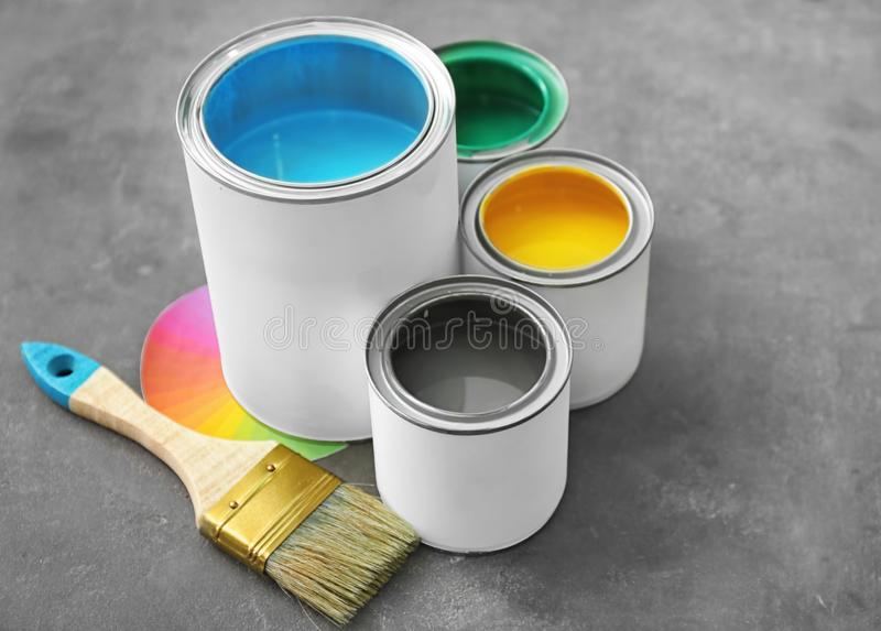 Cans of paint and brush on grey background royalty free stock photography
