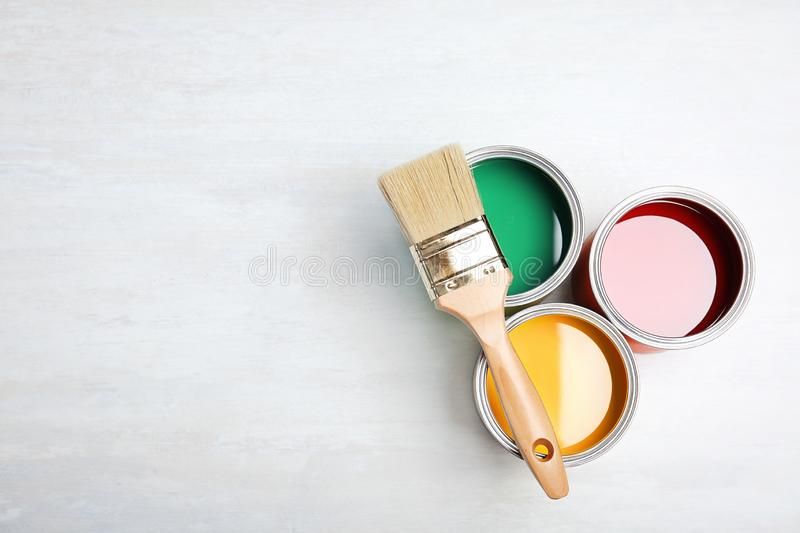 Cans with paint and brush on light background, top view. stock photo