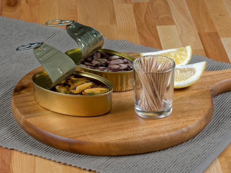 Open tin cans of mussels and octopus on a rustic wooden board. Cans of preserves with mussels and octopus on a rustic wooden board, with lemon slices and royalty free stock images
